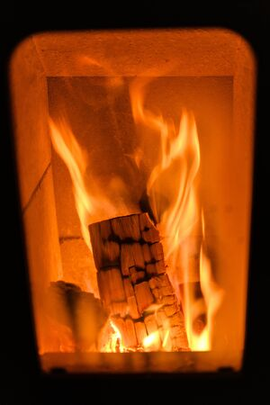 Close-up of a burning log in a wood stove. 写真素材