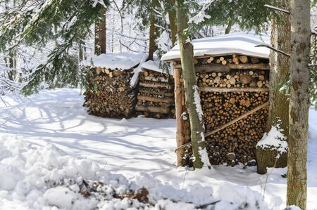 Pile of Firewood Chipped on Each Other Outdoors with Snow.
