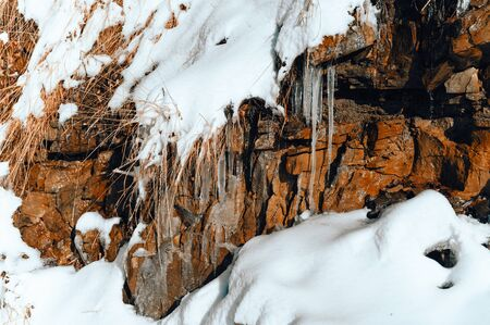 Icy little Stalactite outdoors in nature on an overhang near stones.