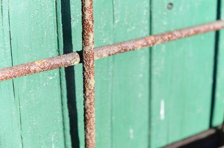 Rusty lattice near green boards. | 写真素材