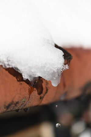 Dripping water from melting snow on the roof. 写真素材