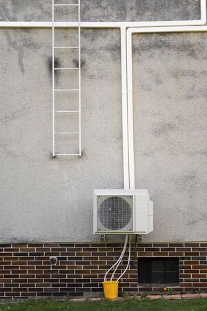 Outdoor air conditioning unit by the wall of a family house. 스톡 콘텐츠