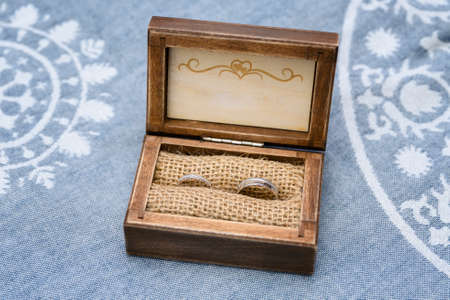 Wooden box with wedding rings made of white gold.
