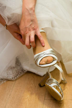 The bride puts on her wedding shoes. Archivio Fotografico