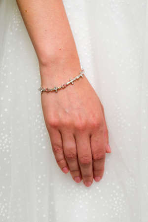 Diamonds on the bracelet on the bride's wrist.