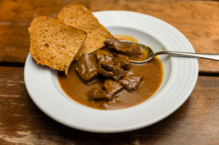 Beef stew with bread on a white plate and spoon. Archivio Fotografico