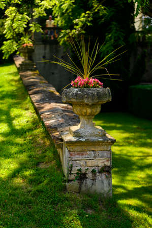 Old stone flower vase with pink flowers and palm tree.