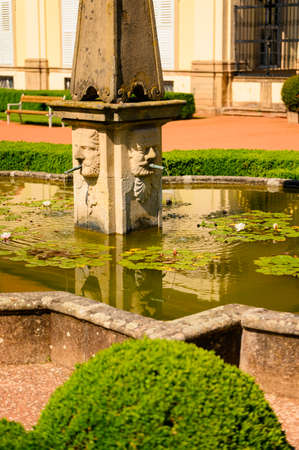Stone fountain with faces, pond and water lilies.