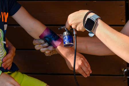 Colorful spray tattoo on a child's hand. Banco de Imagens