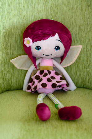 Plush figurine of a sitting fairy with a flower in her hair. Banco de Imagens