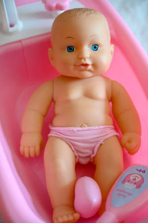 Baby plastic doll in a pink tub.