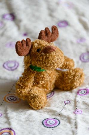 Plush figurine of a sitting moose.