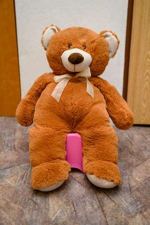 Brown big teddy bear sitting on a potty. Banco de Imagens