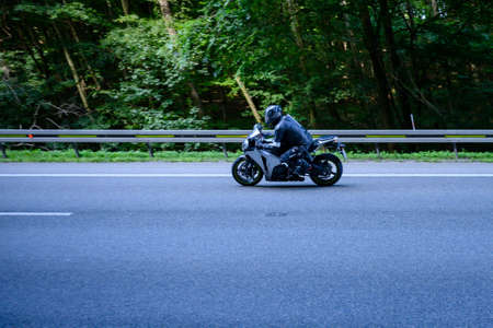 Motorbike riding on the road with barriers and forest in the background.
