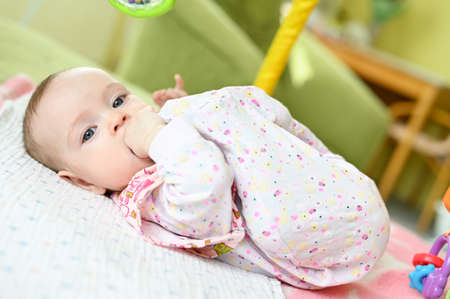 A six month old baby girl lying on her back and sucking her leg.