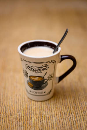 A small mug with coffee and milk and a spoon in detail on the table. Imagens