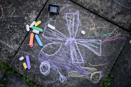 Children's drawing and colored chalks on a tile.