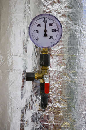 Circular analog pressure gauge with scale on the pipe. Reklamní fotografie