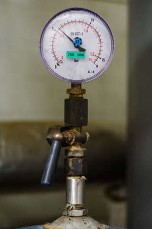 Circular analog pressure gauge with scale on the pipe. Imagens