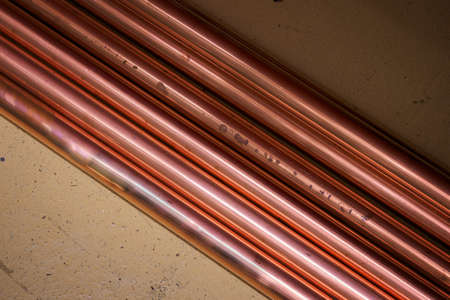 Copper pipes lying on the floor.