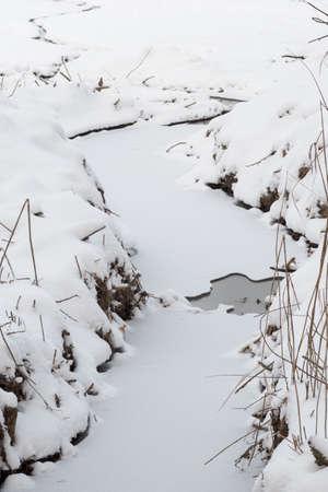 Frozen river with snow receding. Archivio Fotografico