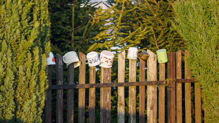 Colorful cups on a wooden fence among green trees.