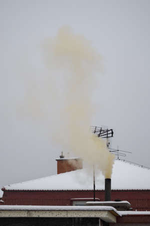 Yellowish smoke coming out of the chimney and a snowy roof in the background.