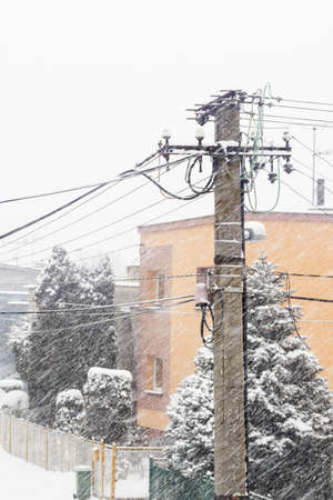 Concrete pole with cables in winter with falling snow. Archivio Fotografico