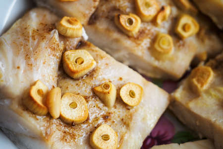 Fish fillet on a plate baked with garlic.