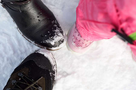 The shoes of a man, woman and child in the snow with each other toes.