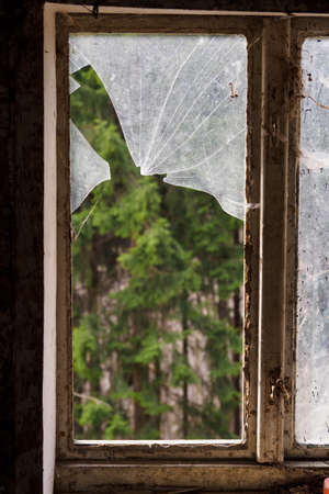 Broken window in a wooden old frame in a wooden house. Stock Photo