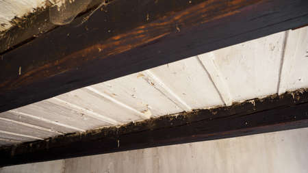 Old ceiling between beams near a wooden house with white paint. Stock Photo