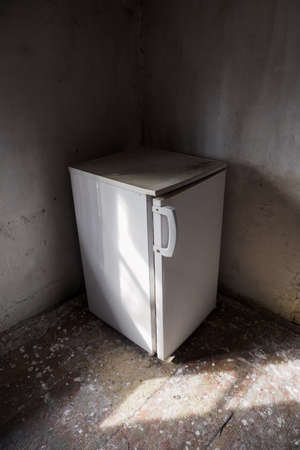 New refrigerator in the old and abandoned interior of the house.
