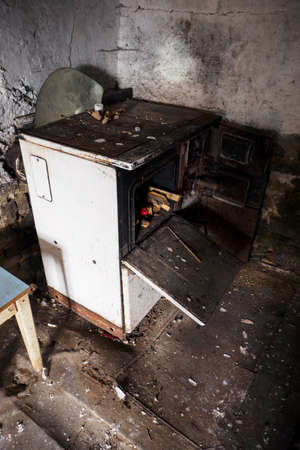 Old metal furnace in a dirty interior.