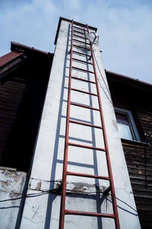 Chimney with metal ladder and antenna near the building. Stock Photo