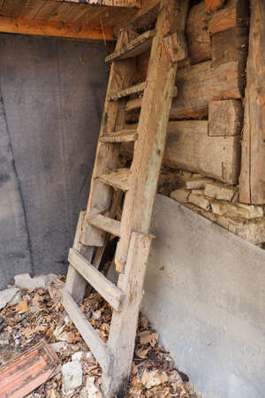 Crumbling wooden stairs outside near a wooden house.