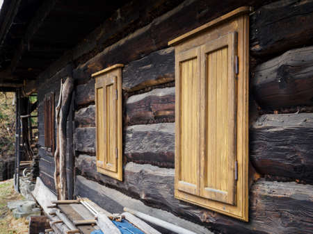 Wooden bright shutters on a wooden house.