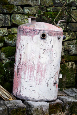 Discarded metal water tank laid outside.