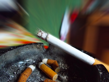 Ashtray and cigarette on a blurred background photo