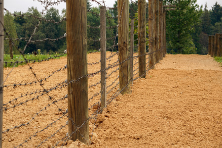 barbed wire fence: Barbed wire fence stretched on a wooden post Stock Photo