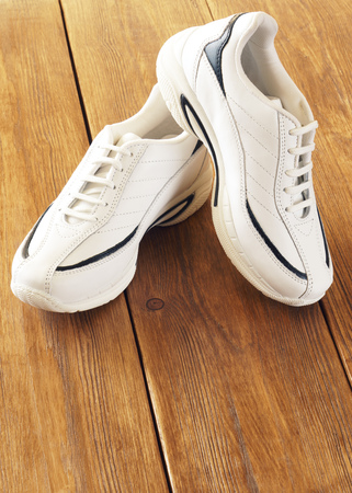 footgear: White sports shoes on a wooden background Stock Photo