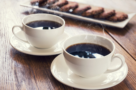 coffee cups: Two cups of hot coffee