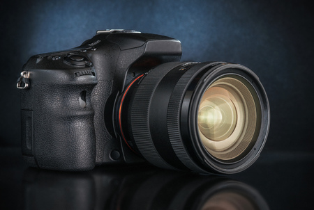 Studio shot of a digital SLR camera with a lens.