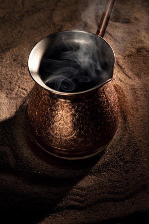 Boiling coffee in copper Turkish coffee brewing pot on the sand Banco de Imagens