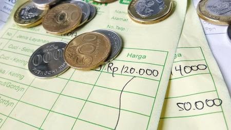 インドネシア ルピアとシンガポール ドル コインと請求書支払い領収書計算資料の図 写真素材