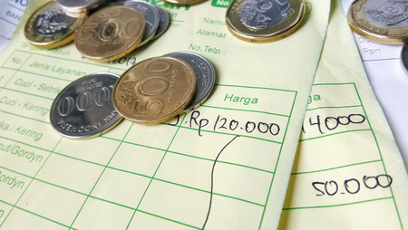 Illustration for payment receipt calculation article with Indonesia rupiah and singapore dollar coins and invoices