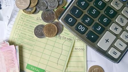 トップ ビューフラットは、インドネシア ルピアとシンガポール ドル硬貨、計算請求書と支払い領収書計算資料の図のレイアウト 写真素材