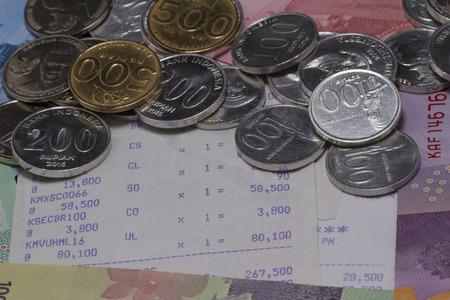 お金とコイン、紙幣やレシート用紙で支払いが示されて 写真素材