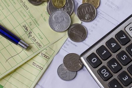 インドネシアルピアとシンガポールドル硬貨、電卓、トップビューフラットレイの請求書との支払い領収書の計算 写真素材