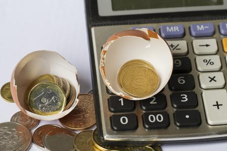 事業投資の計算金融ビジネス プランニング ・ ビジネスのスタートアップは、卵の殻、電卓、コインとイラスト